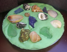 Play dough coaster with rocks and shells